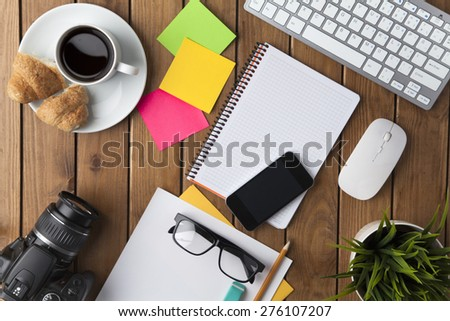 Office desk table with keyboard, supplies, camera and flower - stock photo
