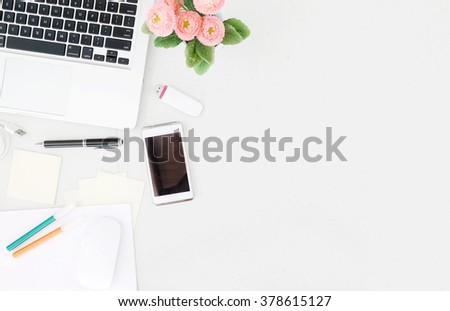 Office desk table with laptop, office supplies and flower pot. Top view with copy space. - stock photo
