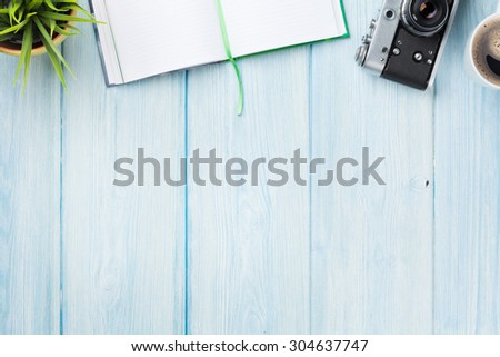 Office desk table with notepad, camera, coffee and flower. Top view with copy space - stock photo