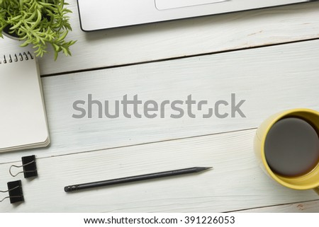 Office desk table with supplies. Top view. Copy space for text. Notepad, pencil, laptop, flower and cup - stock photo