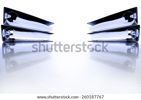 Office desk with business binders full of papers - stock photo