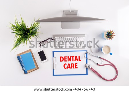 Office desk with DENTAL CARE paperwork and other objects around, top view - stock photo