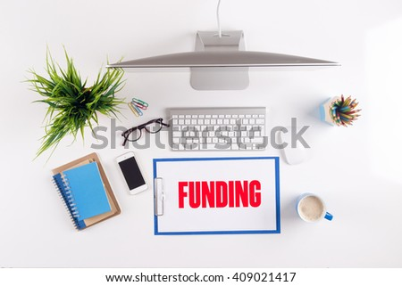 Office desk with FUNDING paperwork and other objects around, top view - stock photo