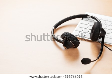 Office desk with headset and pc. Call center support table. Veiw with copy space - stock photo