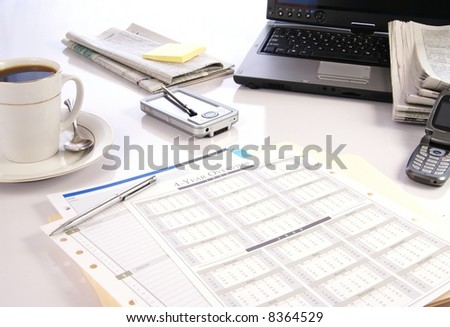 Office desk with laptop computer, newspapers, coffee and misc work materials - stock photo