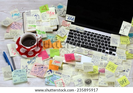 Office desk with laptop covered by post it papers - stock photo