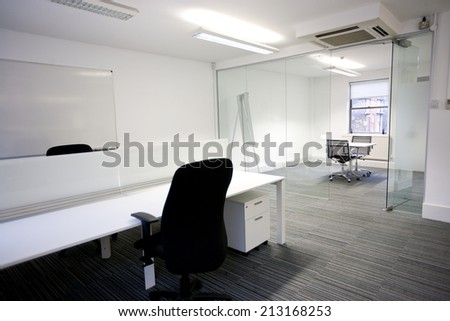 Office desk with meeting room in background - stock photo