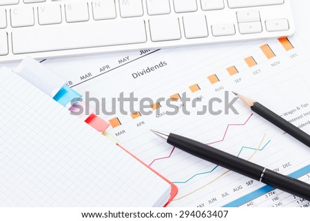 Office desk with reports, computer, supplies and notepad closeup - stock photo