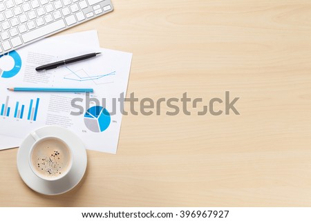 Office desk workplace with pc, charts and coffee on wooden table. Top view with copy space - stock photo