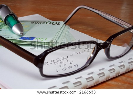 Office desktop with pen, book, eye-glasses and money - stock photo