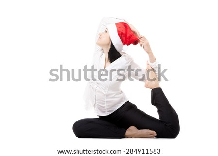 Office female in white shirt and red Santa Claus Christmas hat, in yoga variation of eka pada Rajakapotasana (King Pigeon Pose) - feet hooks one of the arms, isolated - stock photo