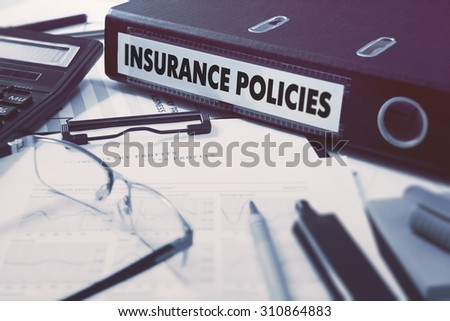 Office folder with inscription Insurance Policies on Office Desktop with Office Supplies. Business Concept on Blurred Background. Toned Image. - stock photo