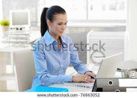 Office girl working on laptop computer at desk, looking at monitor, smiling.? - stock photo