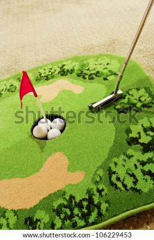Office golf - golf ball and putter - stock photo