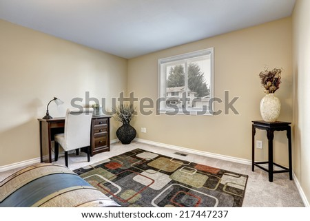 Office interior with wooden desk and white chair. Colorful rug on the carpet floor and small table with flower pot - stock photo