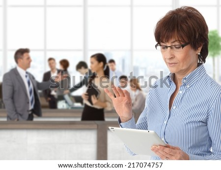Office life senior businesswoman with tablet - stock photo