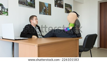 Office Man Taking a Break at His Work Area, Putting His Feet on the Table with Stuffed Toy. - stock photo