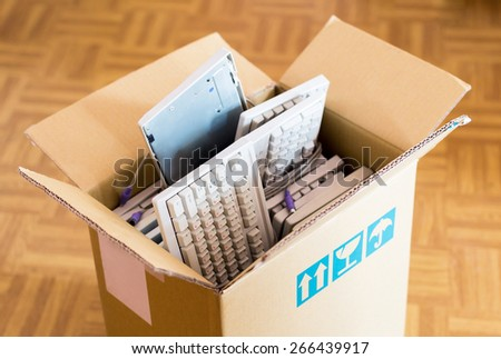 Office move concept - cardboard box with lots of computer keyboards on the wooden floor - stock photo