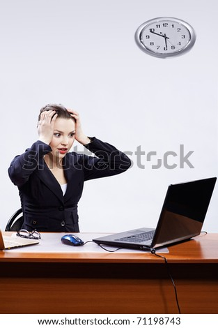 office portrait of beautiful shocked business woman sitting at her workplace with two laptops on gray - stock photo