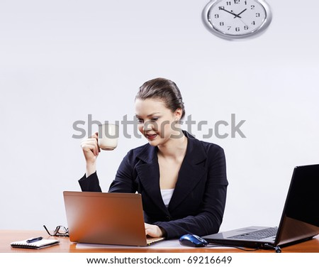 office portrait of beautiful young business woman at her workplace with two laptops having coffee break - stock photo