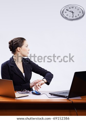 office portrait of beautiful young business woman sitting at her workplace with two laptops on gray and regulating her watches with clocks on wall - stock photo