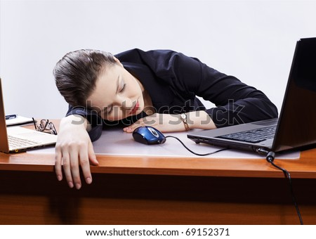 office portrait of beautiful young business woman sleeping at her workplace between two laptops on gray - stock photo