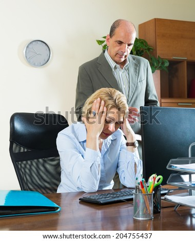 Office scene with angry chief and careless elderly secretary - stock photo