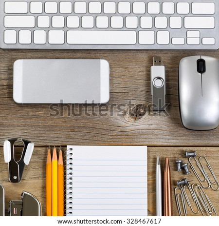 Office setting with keyboard and work supplies on rustic wooden desk - stock photo