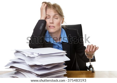 Office shot of heavy workload concept with pile of paper and woman worrying about the amount of work.  chained to desk - stock photo