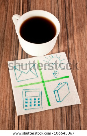 Office signs on a napkin and cup of coffee - stock photo