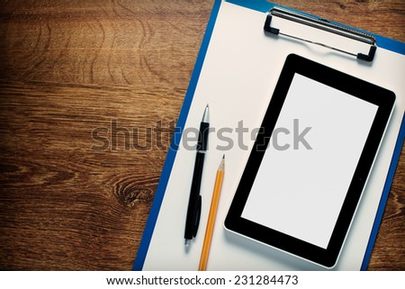 Office supplies laid out ready for a meeting with a tablet viewed overhead with a visible blank screen on a clipboard with paper,pen and pencil - stock photo