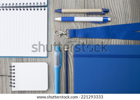 Office supply collection - highlighter, pencil, ball pens, notebooks and lanyard - on brown wooden table. - stock photo