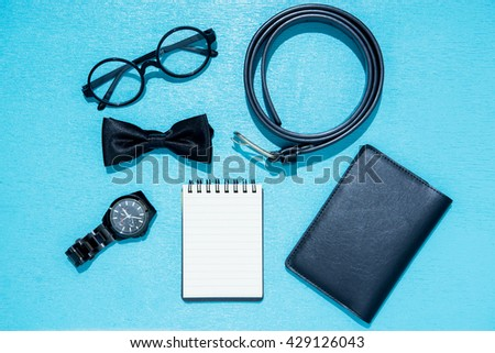 Office table desk with black set of supplies, note book, pen, paper, glasses, bow tie, Watch, wallet, heart on blue background. Top view and copy space for text. - stock photo