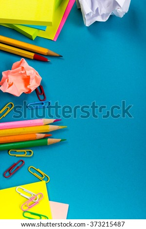 Office table desk with set of colorful supplies, white blank note pad, cup, pen, crumpled paper, flower on blue background. Top view and copy space for text - stock photo