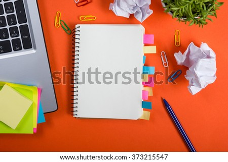 Office table desk with set of colorful supplies, white blank note pad, cup, pen, crumpled paper, flower on red background. Top view and copy space for text - stock photo