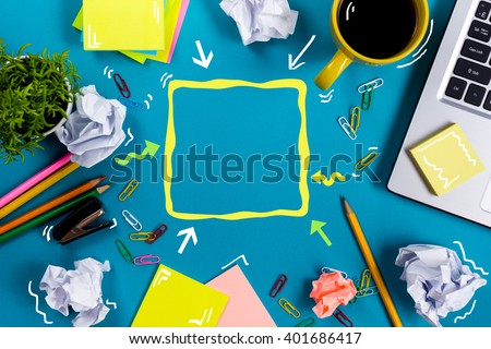 Office table desk with supplies, white blank note pad, cup, pen, pc, crumpled paper, flower on blue background. Top view - stock photo