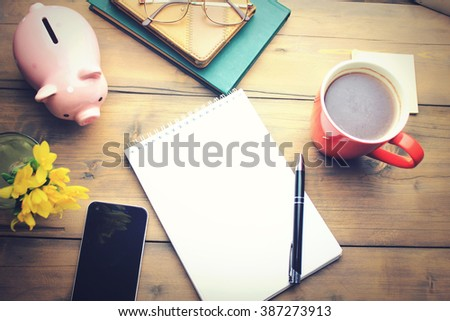 Office table with a coffee cup, a plan on notepad - stock photo