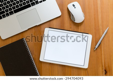 Office table with digital tablet showing a blank screen for advertising - stock photo