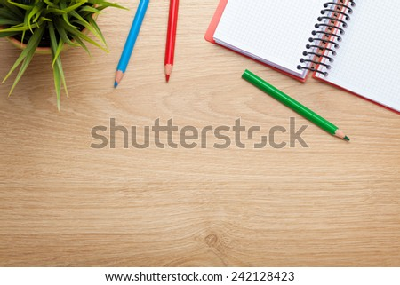 Office table with flower, blank notepad and colorful pencils. View from above with copy space - stock photo