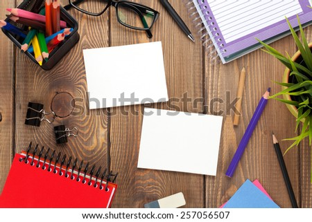 Office table with flower, supplies and two blank photo frames. View from above with copy space - stock photo