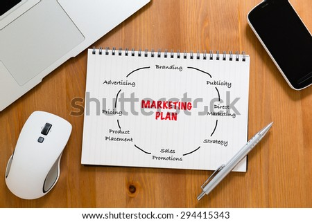 Office table with handbook drafting about marketing planning - stock photo