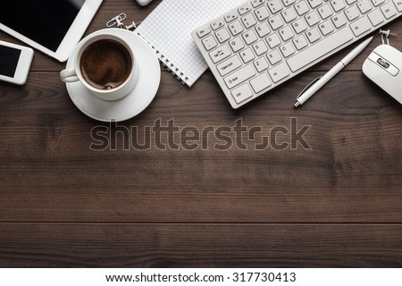 office table with notebook, computer keyboard, mouse, cup of coffee, tablet pc and smartphone. copy space - stock photo