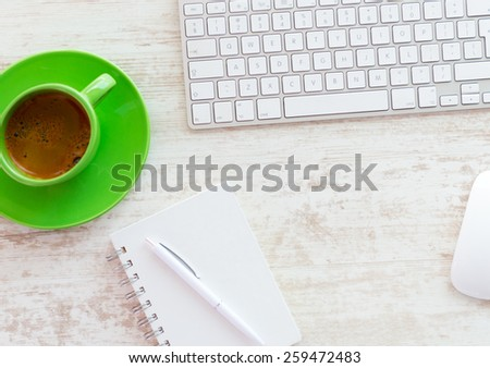 Office table with notepad, computer and coffee cup - stock photo