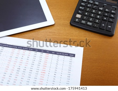 Office table with tablet, calculator and data chart - stock photo