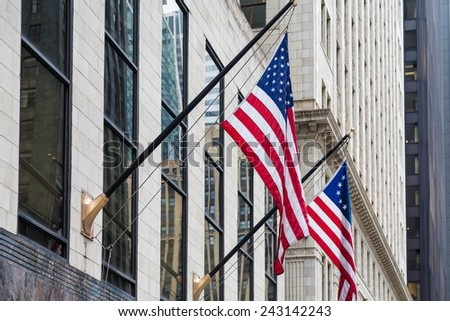 Office tower in Chicago with American flags flying out front. - stock photo
