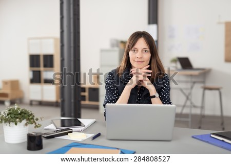 Office Woman Sitting at her Desk with Laptop Computer, Leaning on her Hands in Crossed While Smiling at the Camera. - stock photo