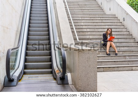 Office woman working in the stairs near scalator with tablet - stock photo