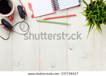 Office wooden desk with notepad, coffee cup and headphones. Top view with copy space - stock photo