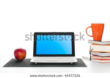 office work desk with laptop computer, pile of books, cup of coffee and apple - stock photo