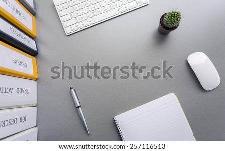 Office work space on grey desk with cactus and folders. From above view on grey wooden desk with well organized office supplies: colored folders, notepad, keyboard, computer mouse and cactus - stock photo